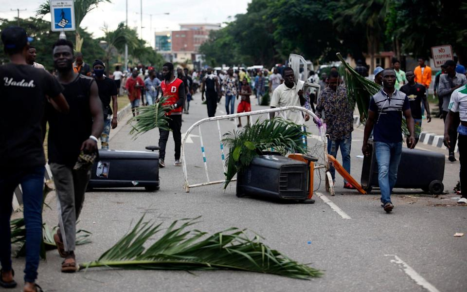 Protesters walk through a barricade along a road during a protest - AKINTUNDE AKINLEYE/EPA-EFE/Shutterstock