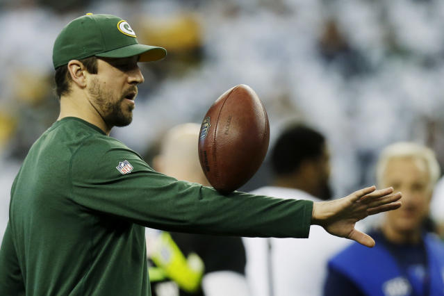 Green Bay Packers quarterback Aaron Rodgers plays with the ball before an NFL football game, Sunday, Dec. 15, 2013, in Arlington, Texas. (AP Photo/Tim Sharp)