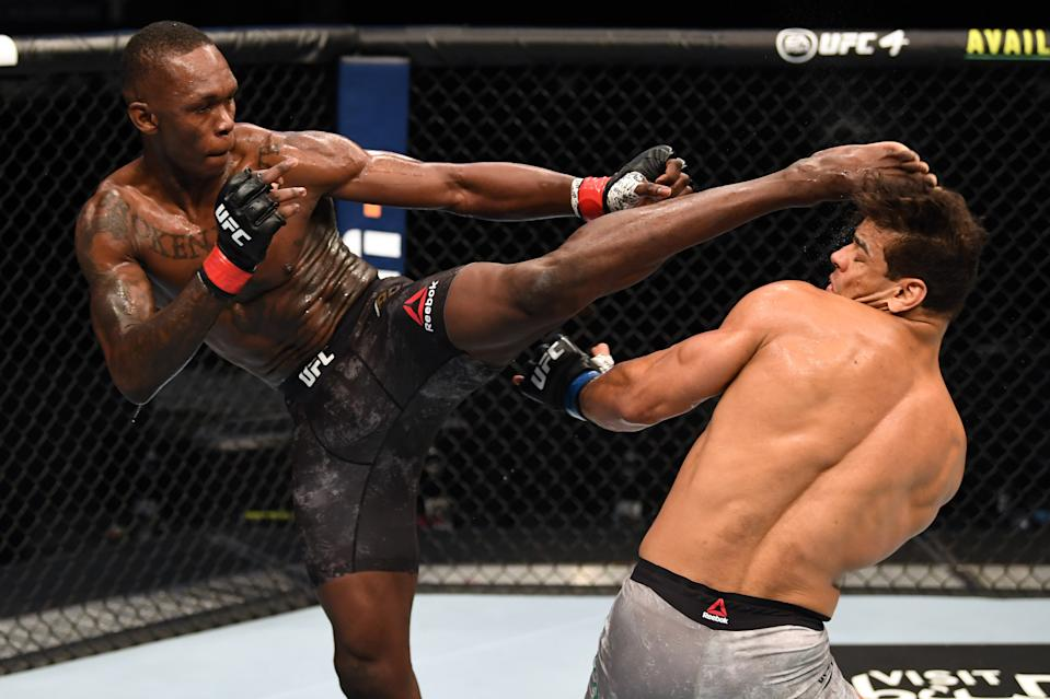 ABU DHABI, UNITED ARAB EMIRATES - SEPTEMBER 27:  (L-R) Israel Adesanya of Nigeria kicks the head of Paulo Costa of Brazil in their middleweight championship bout during UFC 253 inside Flash Forum on UFC Fight Island on September 27, 2020 in Abu Dhabi, United Arab Emirates. (Photo by Josh Hedges/Zuffa LLC)