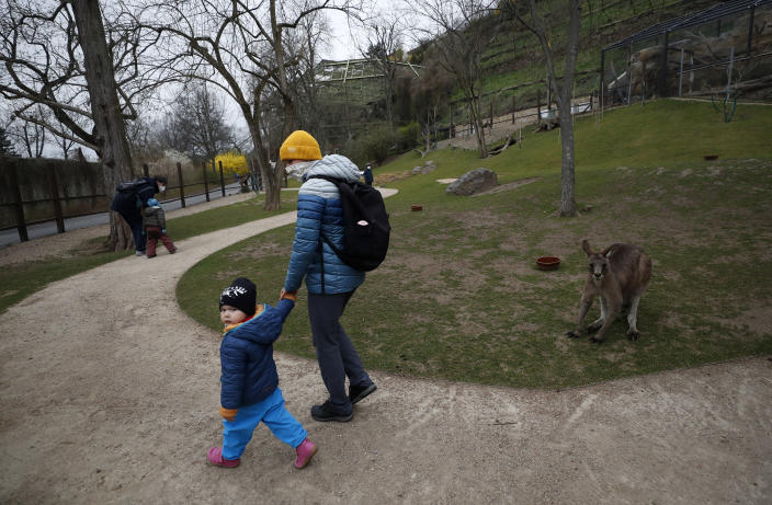 Visitors walk past a kangaroo at an enclosure at the zoo in Prague, Czech Republic, Monday, April 12, 2021. The Czech government has agreed to start easing the tight lockdown, caused by the COVID-19 pandemic, in one of the hardest-hit European countries. Children up to the fifth grade will be back at schools while the stores selling clothes and shoes for kids, laundries, outdoor farmers markets, zoo and botanical gardens are reopened. (AP Photo/Petr David Josek)