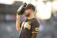 San Diego Padres first baseman Eric Hosmer uses his glove as a shield against intense sun shining on to the infield in the third inning of a baseball game against the Colorado Rockies Monday, June 14, 2021, in Denver. (AP Photo/David Zalubowski)
