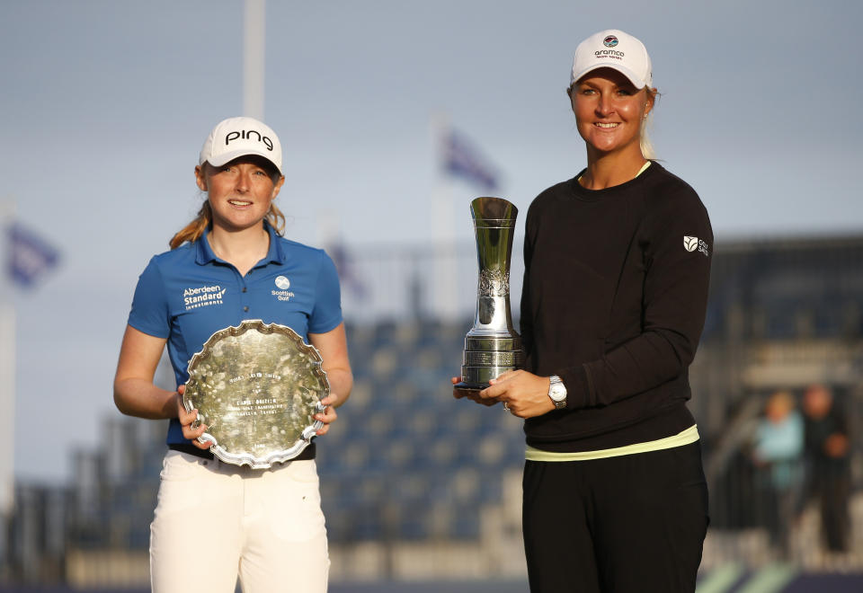 Sweden's Anna Nordqvist holds her trophy and celebrates after winning the AIG Women's Open with the amateur winner, Scotland's Louise Duncan
