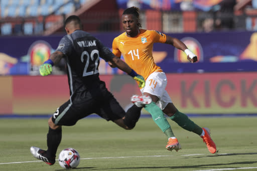 South Africa's Ronwen Williams, left, clears the ball past Ivory Coast's Jonathan Kodjia during the African Cup of Nations group D soccer match between Ivory Coast and South Africa in Al Salam Stadium in Cairo, Egypt, Monday, June 24, 2019. (AP Photo/Hassan Ammar)