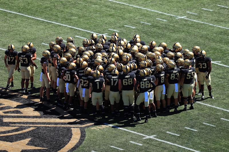 Army football players huddle near the logo on the field.