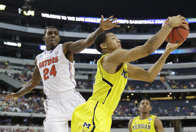 Michigan's Trey Burke (3) grabs a rebound as Florida's Casey Prather (24) defends during the second half of a regional final game in the NCAA college basketball tournament, Sunday, March 31, 2013, in Arlington, Texas. (AP Photo/David J. Phillip)