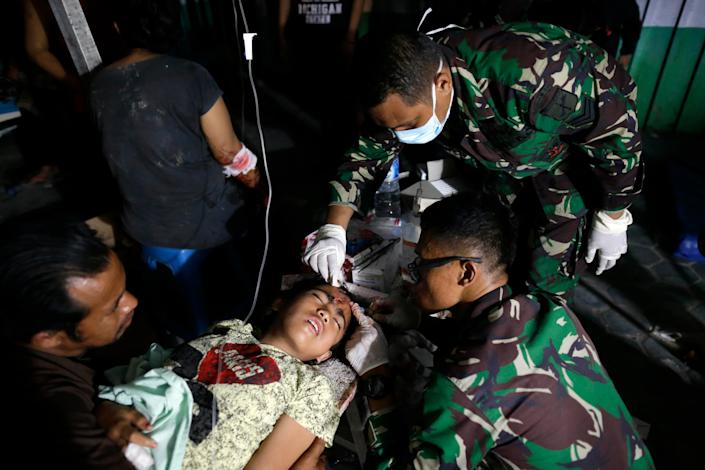 <p>An Indonesian earthquake survivor gets medical treatment outside a military hospital in Palu, Central Sulawesi, Indonesia, Sept. 29, 2018. (Photo: Mast Irham/EPA-EFE/REX/Shutterstock) </p>