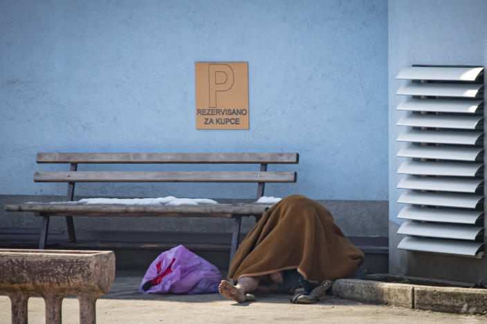 A migrant sits on the pavement to warm up outside the Miral camp, in Velika Kladusa, Bosnia, Wednesday, April 7, 2021. Bosnia is seeing a rise in coronavirus infections among migrants and refugees living in its camps, as it struggles to cope with one of the Balkans' highest COVID-19 death and infection rates among the general population.(AP Photo/Davor Midzic)