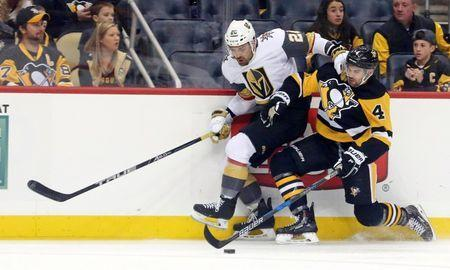 Oct 11, 2018; Pittsburgh, PA, USA; Vegas Golden Knights left wing William Carrier (28) and Pittsburgh Penguins defenseman Justin Schultz (4) battle for the puck along the boards during the first period at PPG PAINTS Arena. Mandatory Credit: Charles LeClaire-USA TODAY Sports