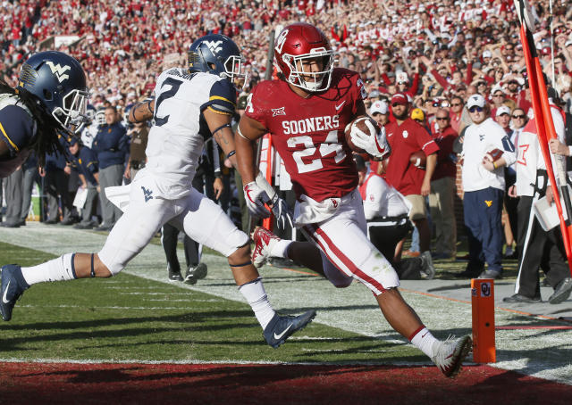 "Oklahoma running back <a class=""link rapid-noclick-resp"" href=""/ncaaf/players/251153/"" data-ylk=""slk:Rodney Anderson"">Rodney Anderson</a> (24) scores in front of West Virginia safety Kenny Robinson (2) in the first quarter of an NCAA college football game in Norman, Oklahoma, Saturday, Nov. 25, 2017. (AP Photo/Sue Ogrocki)"