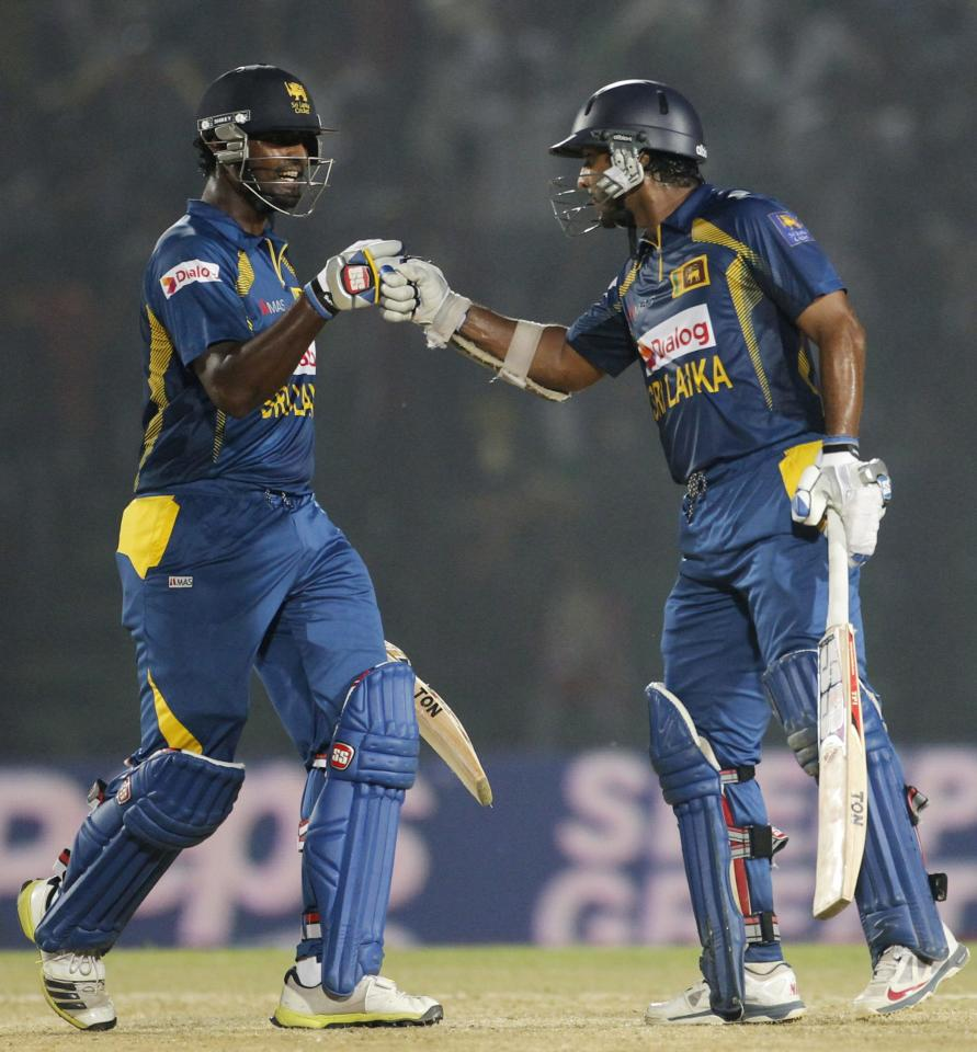 Sri Lanka's Thisara Perera congratulates Kumar Sangakkara (R) as he scored a century against India during their Asia Cup 2014 one-day international (ODI) cricket match in Fatullah February 28, 2014. REUTERS/Andrew Biraj (BANGLADESH - Tags: SPORT CRICKET)