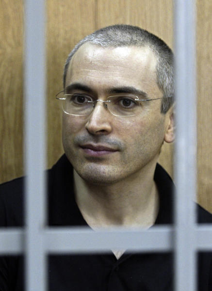 FILE In this Friday, July 30, 2004 file photo former Yukos CEO Mikhail Khodorkovsky sits in a courtroom behind bars in Moscow, Russia. Russian President Vladimir Putin said Thursday Dec. 19, 2013 after his annual news conference that Khodorkovsky will pardon jailed tycoon Mikhail Khodorkovsky. (AP Photo/ Sergey Ponomarev, File)