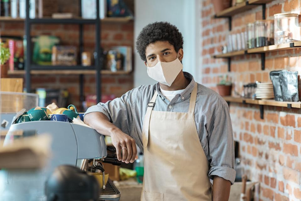 Coffee business, startup and back to normal concept. Young african american guy barista in apron and protective mask with equipment in coffee shop in morning at lockdown, quarantine, coronavirus