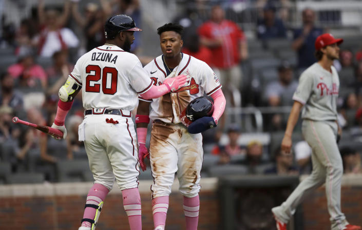 Atlanta Braves' Marcell Ozuna (20) congratulates Ronald Acuna Jr. after Acuna scored against the Philadelphia Phillies in the first inning of a baseball game Sunday, May 9, 2021, in Atlanta. (AP Photo/Ben Margot)