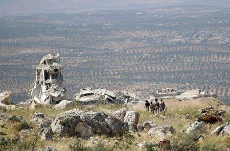 Rebel fighters from the Ahrar al-Sham Islamic Movement walk on a hill in Jabal al-Arbaeen, which overlooks the northern town of Ariha, one of the last government strongholds in the Idlib province May 26, 2015. REUTERS/Khalil Ashawi