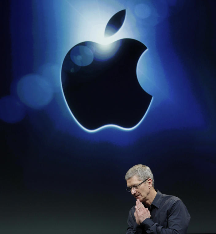 FILE - In this Oct. 4, 2011 file photo, Apple CEO Tim Cook gestures during the introduction of the iPhone 4S, at Apple headquarters in Cupertino, Calif. Apple Inc. is finally using its $98 billion pile of cash to reward shareholders, saying it's instituting both a dividend and share buyback program. (AP Photo/Paul Sakuma, File)