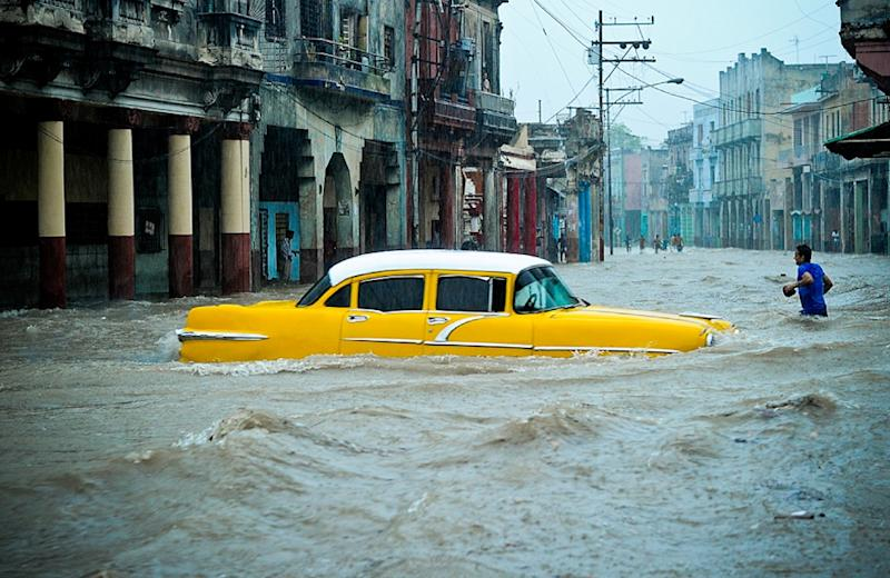 People wade through a flooded street during an intense rainstorm in Havana, on April 29, 2015