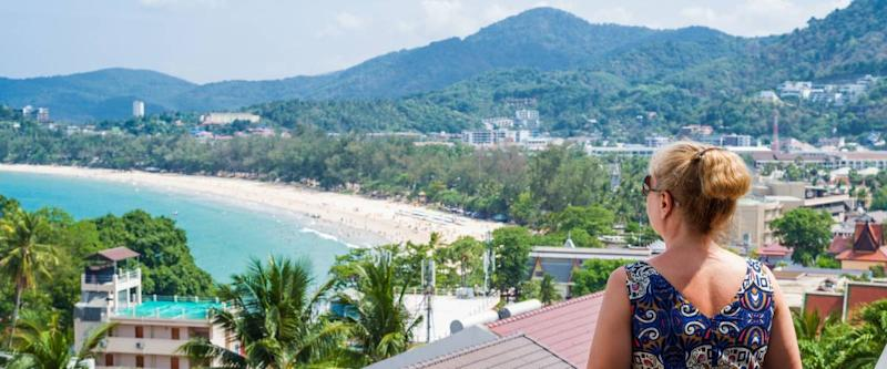 Woman enjoying the views over Kata beach from the hotel balcony. Phuket, Thailand