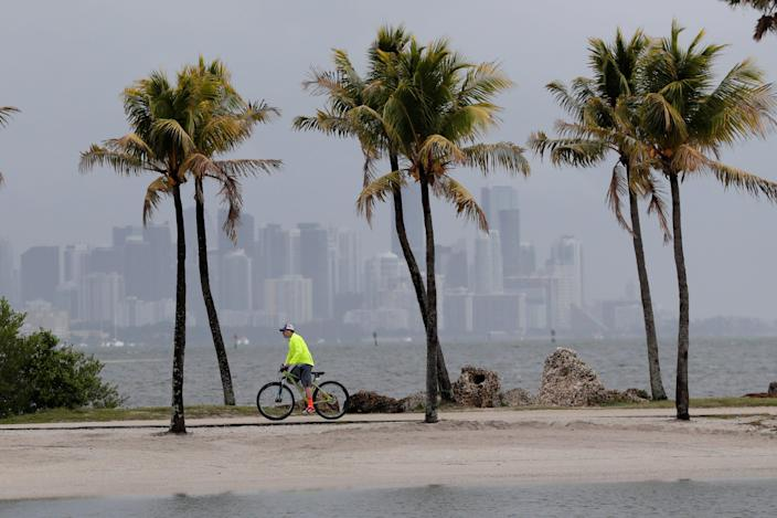 The Miami skyline is shrouded in clouds as a cyclist rides along Biscayne Bay on May 15, 2020. Tropical Storm Arthur formed off the Florida coast over the weekend.