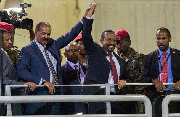 PHOTO: In this July 15, 2018 file photo, Eritrean President Isaias Afwerki and Ethiopian Prime Minister Abiy Ahmed hold hands as they wave at the crowds in Addis Ababa, Ethiopia. (Mulugeta Ayene/AP)