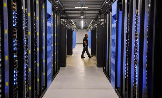 An employee walks past servers at the Facebook Data Center in Forest City, N.C.