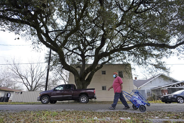 Tico Martinez pulls a cart with cases of donated water back to his apartment, Friday, Feb. 26, 2021, in Houston. Local officials, including Houston Mayor Sylvester Turner, say they have focused their efforts during the different disasters on helping the underserved and under-resourced but that their work is far from complete. (AP Photo/David J. Phillip)