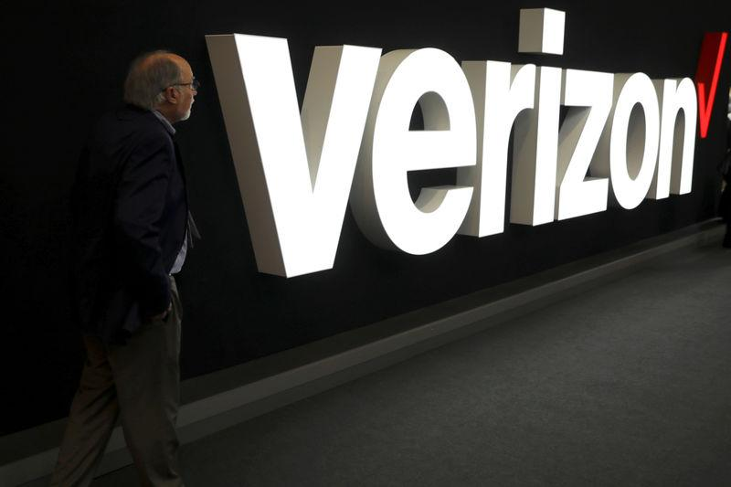 FILE PHOTO: A man stands next to the logo of Verizon at the Mobile World Congress in Barcelona