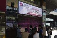 People walk past a bank's electronic board showing the Hong Kong share index at Hong Kong Stock Exchange Tuesday, Oct. 27, 2020. Shares skidded in Asia on Tuesday after surging coronavirus cases and waning hopes for U.S. economic stimulus gave Wall Street its worst day in a month. (AP Photo/Vincent Yu)