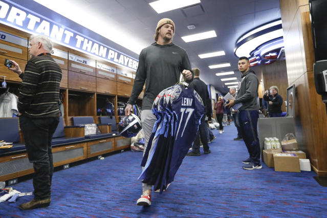 Tennessee Titans offensive tackle Taylor Lewan, center, gathers items as players clean out their lockers Monday, Jan. 20, 2020, in Nashville, Tenn. The Titans lost the AFC Championship NFL football game Sunday to the Kansas City Chiefs. (AP Photo/Mark Humphrey)