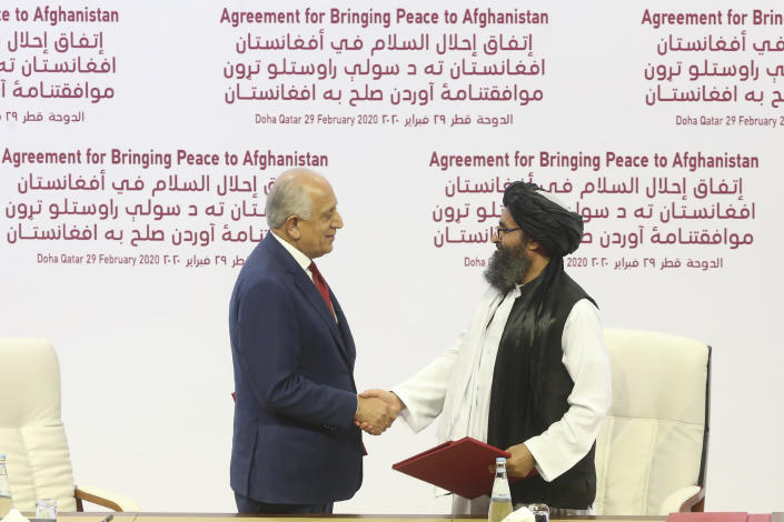 U.S. peace envoy Zalmay Khalilzad, left, and Mullah Abdul Ghani Baradar, the Taliban group's top political leader shake hands after signing a peace agreement between Taliban and U.S. officials in Doha, Qatar on Feb. 29, 2020. (Hussein Sayed/AP)