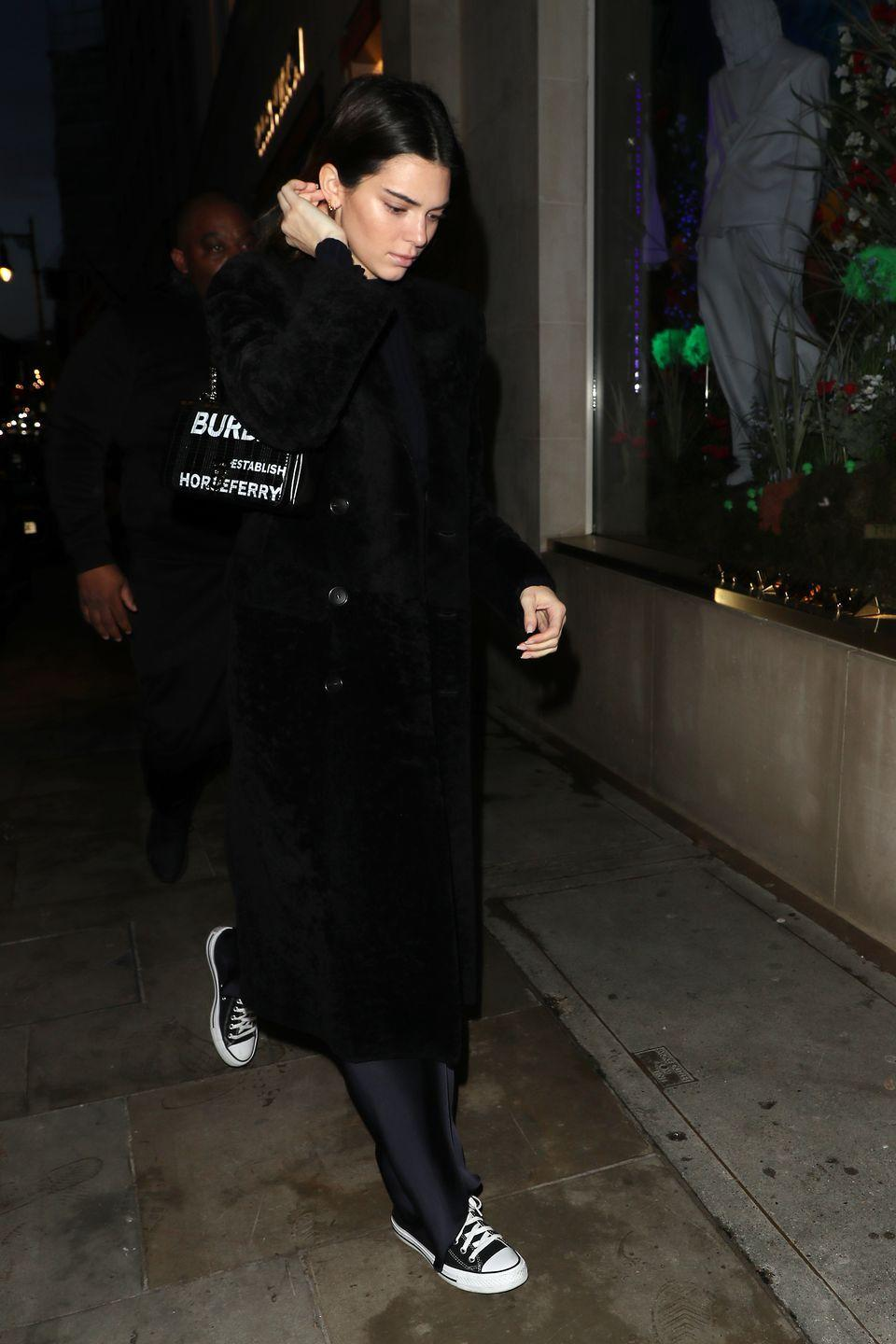 """<p>The model was seen shopping at Louis Vuitton before heading to the Burberry head office for a fitting during London Fashion Week. The star wore an all-black, Matrix look which consisted of black Converse trainers, black satin trousers, a black overcoat, black jumper and carried a black Burberry bag for the outing. </p><p><a class=""""link rapid-noclick-resp"""" href=""""https://go.redirectingat.com?id=127X1599956&url=https%3A%2F%2Fwww.net-a-porter.com%2Fgb%2Fen%2Fproduct%2F1148911%3Fgclsrc%3Daw.ds%26gclsrc%3Daw.ds%26cm_mmc%3DGoogle-ProductSearch-UK--c-_-NAP_EN_UK_PLA-_-NAP%2B-%2BUK%2B-%2BGS%2B-%2BSale%2B-%2B1MD%2B-%2BDesigner%2B-%2BFW19%2B-%2BCSS--Sale%2B-%2BClothing_INTL%26gclid%3DCj0KCQiAkKnyBRDwARIsALtxe7hDXaL3eZfLLyvZ_uIIjz8iBgOn3jtd79vc41188SFwuhBw37IHbHEaAhpxEALw_wcB&sref=https%3A%2F%2Fwww.elle.com%2Fuk%2Ffashion%2Fcelebrity-style%2Farticles%2Fg2543%2Fkendall-jenner%2F"""" rel=""""nofollow noopener"""" target=""""_blank"""" data-ylk=""""slk:SHOP SILK-SATIN TROUSERS"""">SHOP SILK-SATIN TROUSERS</a></p>"""
