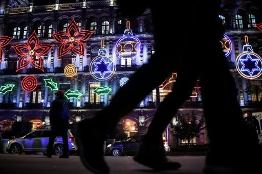 Projectors are used to shine colorful Christmas-themed designs on a government building in Mexico City's Zocalo square