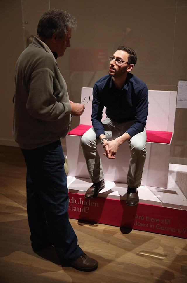 "BERLIN, GERMANY - APRIL 04: Bill Glucroft, an American Jew living in Berlin, chats to visitors from his box in the ""live exhibit"" portion of the exhibition ""The Whole Truth - Everything You Always Wanted To Know About Jews . . . "" at the Juedisches Museum (Jewish Museum) on April 4, 2013 in Berlin, Germany. The exhibition presents every-day aspects of Jewish life, poses simple questions answered with exhibits and challenges certain stereotypes. However its live exhibit, which features a Jewish person who sits in a plastic enclosure open on one side for several hours a day to answer visitors' questions, has sparked criticism from some Jewish groups. (Photo by Sean Gallup/Getty Images)"