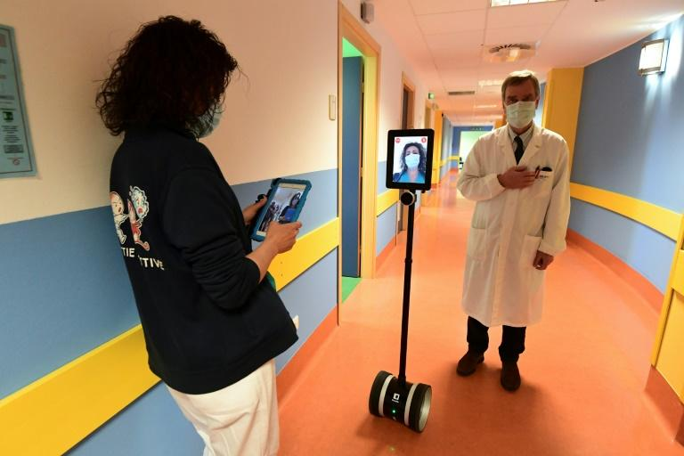 A nurse (L) manipulates a robot called Ivo used to help patients infected by the novel coronavirus at the Circolo di Varese hospital in Italy amid the the spread of the pandemic (AFP Photo/Miguel MEDINA)