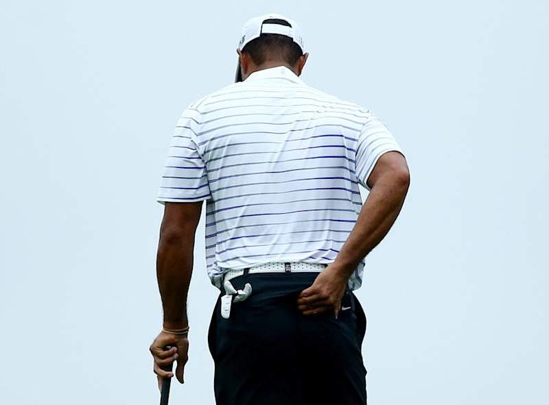 Tiger Woods rubs his back before hitting his second shot on the 17th hole during the second round of the PGA Championship in Louisville on August 8, 2014
