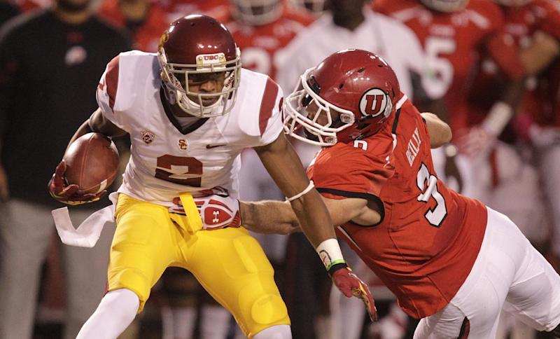 Southern California wide receiver Robert Woods (2) carries the ball as he breaks a tackle from Utah linebacker Trevor Reilly (9) in the first quarter during an NCAA college football game Thursday, Oct. 4, 2012, in Salt Lake City.  (AP Photo/Rick Bowmer)