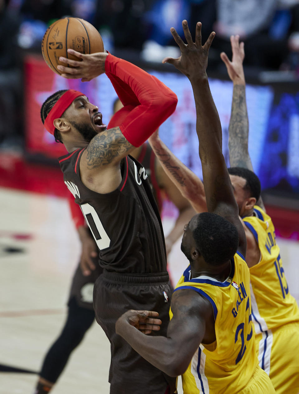 Portland Trail Blazers forward Carmelo Anthony, left, shoots over Golden State Warriors forward Draymond Green, front, and guard Mychal Mulder during the second half of an NBA basketball game in Portland, Ore., Wednesday, March 3, 2021. (AP Photo/Craig Mitchelldyer)