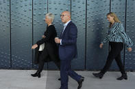 Ria van der Steen, left, who lost her father and stepmother in the MH17 crash, center right, arrives to give testimony in court in the trial of four men charged with murder over the downing of Malaysia Airlines flight MH17, at Schiphol airport, near Amsterdam, Netherlands, Monday Sept. 6, 2021. Relatives of some of the 298 people killed in the downing of Malaysia Airlines flight MH17 tell a Dutch court about the impact on their lives of the disaster during the trial of three Russians and a Ukrainian charged with involvement in bringing down the Amsterdam-Kuala Lumpur flight more than seven years ago. (AP Photo/Peter Dejong)