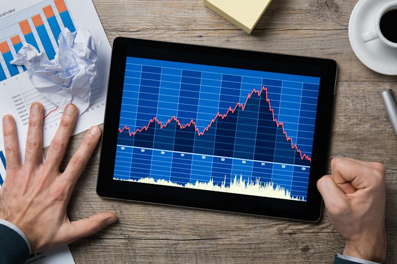 A tablet displaying a falling stock chart, surrounded by a hand splayed out in alarm and a clenched fist