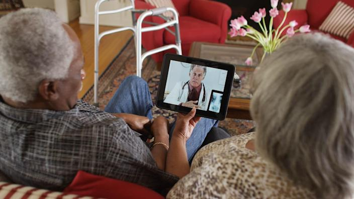 older couple talking with telemedicine doctor on tablet