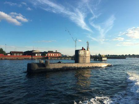 """An unidentified woman stands in the tower of the private submarine """"UC3 Nautilus"""" pictured in Copenhagen Harbor, Denmark August 11, 2017. Picture taken August 11, 2017. Anders Valdsted/Scanpix Denmark via REUTERS"""