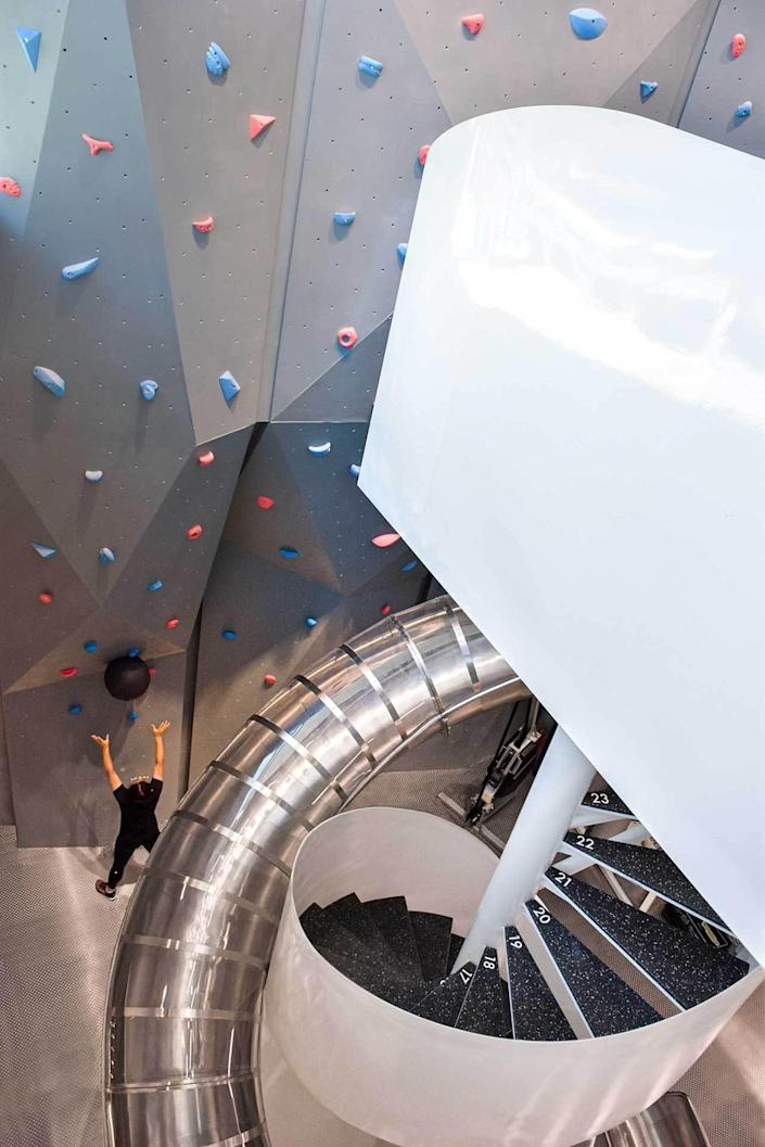 A large climbing wall sits right next to MFIT SPACE 01's spiraling metallic slide.