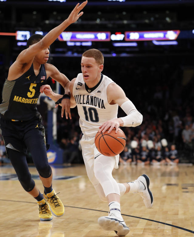 Villanova guard Donte DiVincenzo (10) drives around Marquette guard Greg Elliott (5) during the first half of an NCAA college basketball game in the quarterfinals of the Big East men's tournament in New York, Thursday, March 8, 2018. (AP Photo/Kathy Willens)