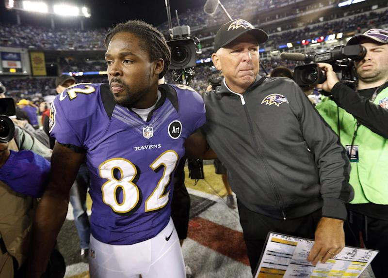 Baltimore Ravens' Torrey Smith, left, embraces Ravens offensive coordinator Cam Cameron after an NFL football game against the New England Patriots in Baltimore, Sunday, Sept. 23, 2012. Baltimore won 31-30. (AP Photo/Patrick Semansky)