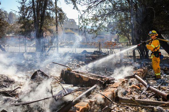 A firefighter sprays the remains of a house destroyed by a wildfire in Lower Lake, California, Aug. 15, 2016.