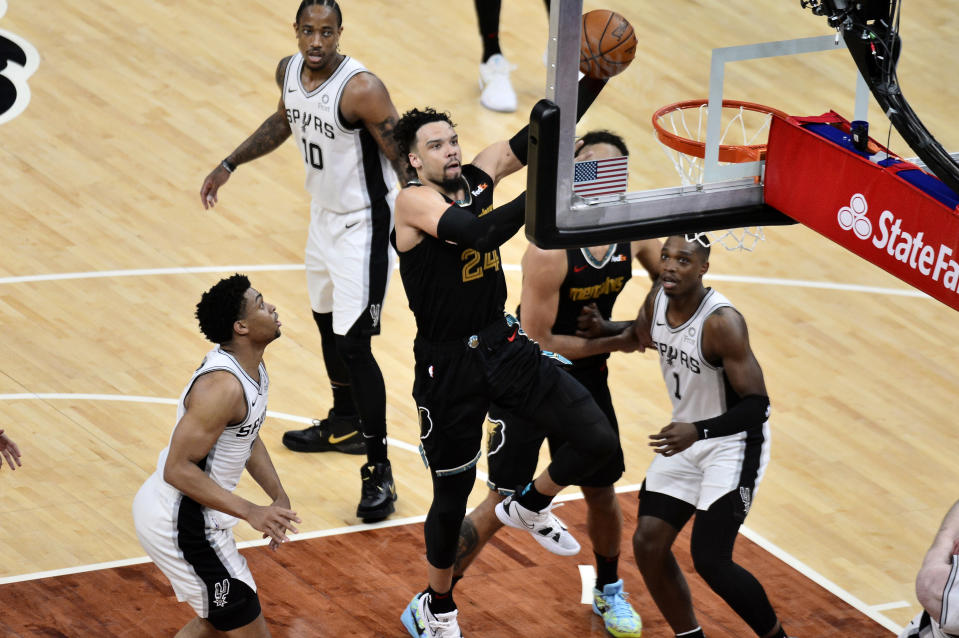 Memphis Grizzlies forward Dillon Brooks (24) shoots next to San Antonio Spurs guard Lonnie Walker IV (1) and forward Keldon Johnson during the second half of an NBA basketball Western Conference play-in game Wednesday, May 19, 2021, in Memphis, Tenn. (AP Photo/Brandon Dill)