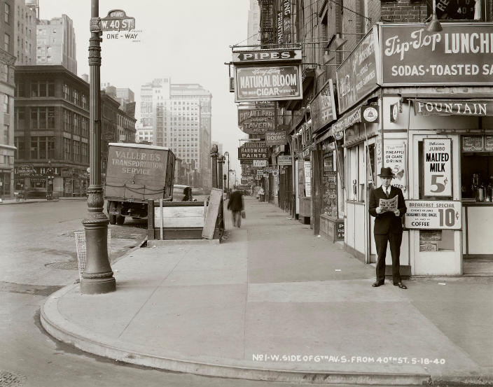"""In this May 18, 1940 photo provided by the New York City Municipal Archives, a man reads a newspaper on New York's 6th Ave. and 40th St, with the headline: """"Nazi Army Now 75 Miles From Paris."""" Over 870,000 photos from an archive that exceeds 2.2 million images have been scanned and made available online, for the first time giving a global audience a view of this rich collection that documents life in New York City.  (AP Photo/New York City Municipal Archives, Borough President Manhattan) MANDATORY CREDIT"""