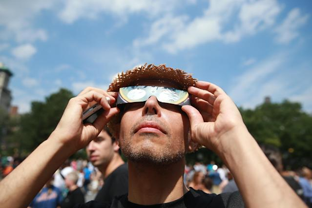 <p>A man checks out the total solar eclipse wearing eclipse glasses in Union Square, New York City, on Aug. 21, 2017. (Gordon Donovan/Yahoo News) </p>