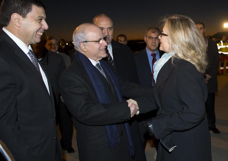 Algerian Foreign Minister Mourad Medelci, centre, greets US Secretary of State Hillary Rodham Clinton, upon her arrival at Houari Boumediene Airport,  in Algiers, Algeria, Monday, Oct. 29, 2012.  US Secretary Secretary of State Hillary Rodham Clinton is on a five-day trip overseas to increase pressure on Mali's al-Qaida-linked rebels and help Balkan nations end long-simmering ethnic and political disagreements. (AP Photo, Saul Loeb, Pool)