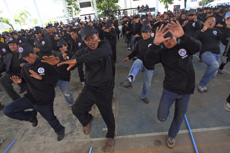 """In this April 3, 2014 photo, black-clad supporters of Thai Prime Minister Yingluck Shinawatra take part in a Thai kickboxing exercise in Udon Thani province, Thailand. Following the directions of a trainer on a nearby stage, they fended off kicks and practiced footwork to loud speakers blaring music typically heard at a Thai kickboxing stadium. It was was part of a two-day training course for farmers, laborers and others in the heart of pro-government """"Red Shirt"""" country - Thailand's rural, poor north and northeast. (AP Photo/Sakchai Lalit)"""
