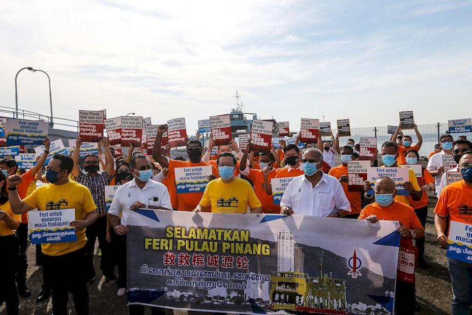 Former Minister of Finance Lim Guan Eng along with VIPs holding the banner 'Selamatkan Feri Kita' before boarding the ferry service for the last time here at Pengkalan Raja Tun Uda Ferry Terminal, December 31, 2020. — Picture by Sayuti Zainudin